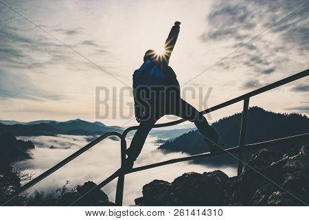Man With Raised Hand On Top Of A Mountain, Concept Of Inspiration, Enthusiasm And Aspiration