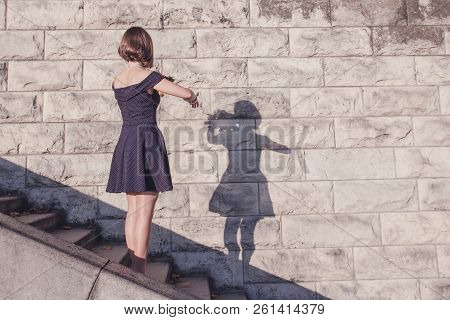 Young Beautiful Brunette Girl In Blue Dress Dancing With Her Shadow On Stone Wall Background, Concep