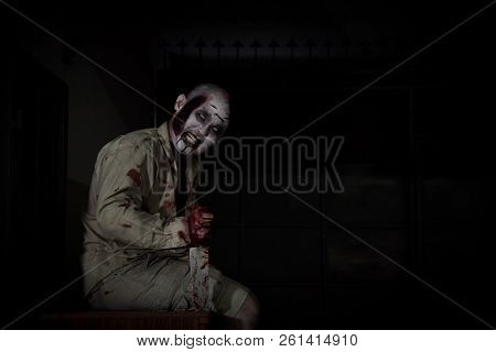 Male Zombie Sitting And Smiles In Dark Room