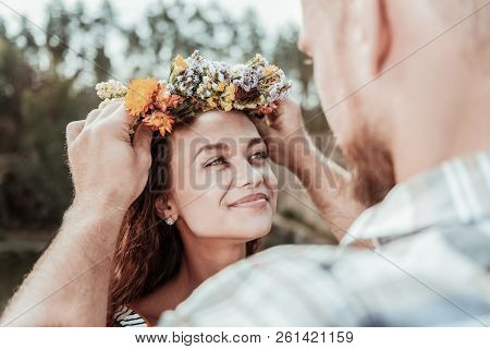 Loving bearded man putting beautiful floral chaplet on head of his appealing woman poster
