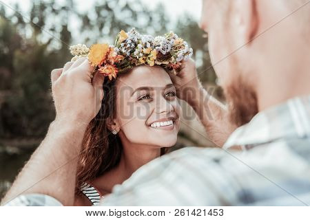 Beautiful green-eyed woman feeling extremely happy receiving nice floral chaplet poster