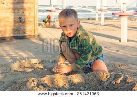 Child Playing In The Sand On The Beach At The Seaside.