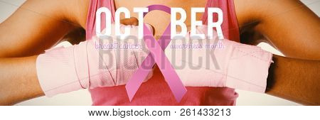 Breast cancer awareness ribbon with text against mid section of woman for breast cancer awareness