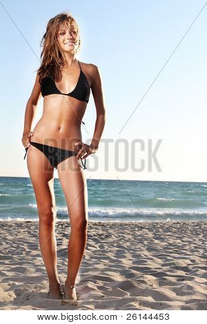young attractive woman in black bikini on sand beach