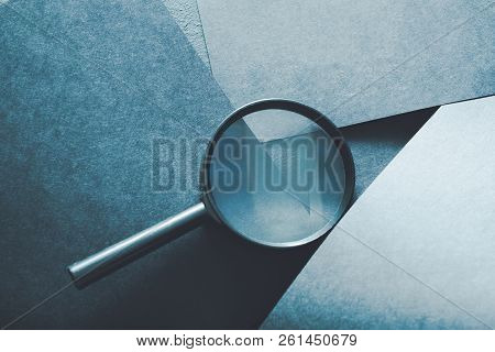 Magnifying Glass. Finding Things Or Detecting Problems Concept. Loupe On Layered Blue Paper Backgrou
