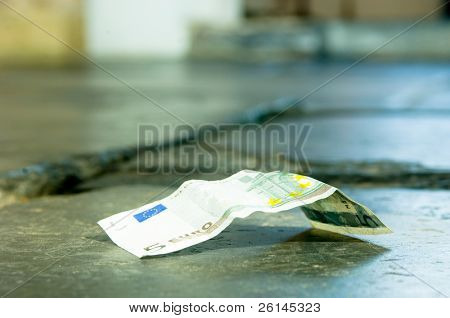 A 5 euro banknote lying on a church floor
