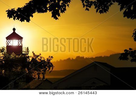 Alki Point lighthouse, looking out over the Olympic Peninsula during a radiant sunset poster