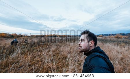 Man With A Manic Expression In Black Jacket Stalking The Victim In The Autumn Forest. Concept Of Aut