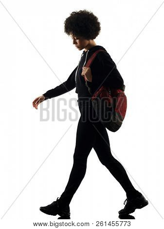 one mixed race african young teenager girl woman walking sadness in studio shadow silhouette isolated on white background