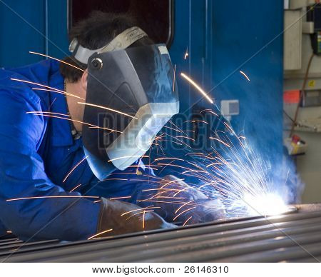 A welder, wearing a protective helmet and fire retardant clothing, working on steel beams