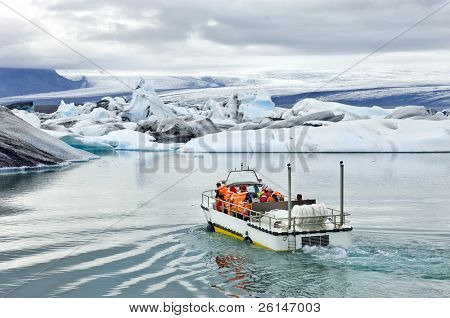 An amphibious vehicle taking tourists for a cruise around the icebergs in the Jokulsarlon glacier lake, where huge chunks of ice from the Vatnajokull glacier float out to the Atlantic ocean