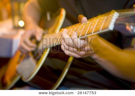 Fingers in motion on the frets of an acoustic guitar