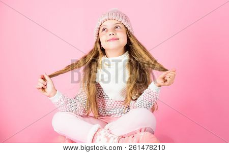 Winter Fashion Concept. Girl Long Hair Relaxing Pink Background. Kid Smiling Fashion Model. Kid Girl