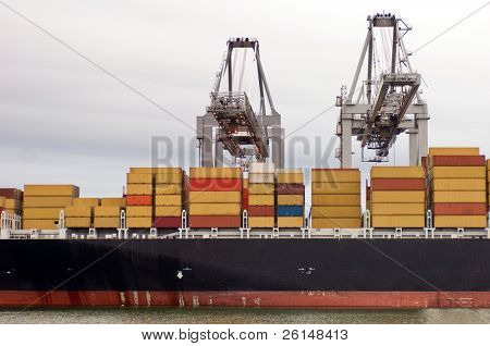 Container ship being unloaded by two large cranes  in the Rotterdam Harbor