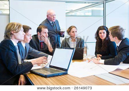 O funcionário mais jovem fazendo uma sugestão durante uma reunião com a equipe e todos, incluindo o senior