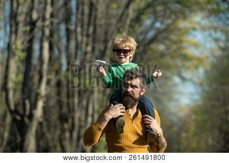 Little Child Playing With Paper Plane On Father Shoulder In Park. Father And Son Playing Games Toget