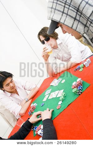 Four people sitting around a table with a red tablecloth for a casual game of poker
