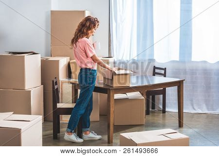 Side View Of Beautiful Woman With Curly Red Hair Unpacking Cardboard Boxes At New Home