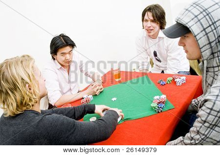 Four people sitting around a square poker table for a private casual game