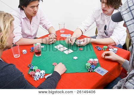 Four people around a table during a poker game