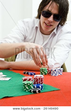 A poker player with huge sunglasses, cunningly smiling and raising the stakes of his game.