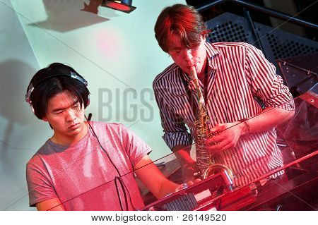 DJ and saxophonist jamming together in a Dee Jay booth at a nightclub