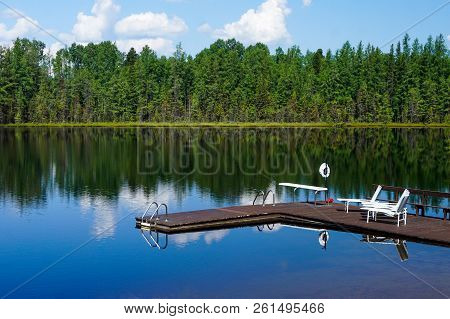 Beautiful Clear Blue Lake Water Reflecting Green Trees And Clouds With Wooden Dock, Ladders, Diving