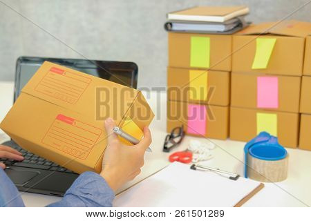 Startup Small Business Owner Hold Cardboard Box At Workplace. Freelance Woman Entrepreneur Seller Pr