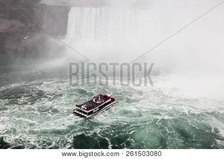 NIAGARA FALLS, ONTARI, CANADA - MAY 29, 2016: Hornblower Niagara Thunder boat with tourists in Niagara Falls view from Canadian sideseen in Niagara Falls.