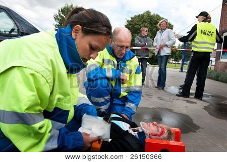 Paramedics providing first aid to an injured woman with police and bystanders in the background poster