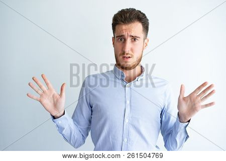 Puzzled Businessman Denying Mistake. Young Man In Formal Shirt Throwing Hands Up And Rejecting Respo