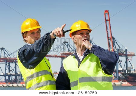Dos estibadores en discusión, frente a un gran puerto industrial