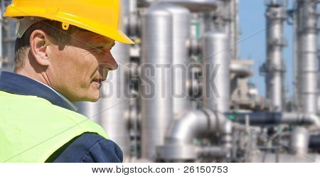 Close up of an engineer wearing a safety vest, blue coveralls, and a hard hat in front of a petrochemical plant