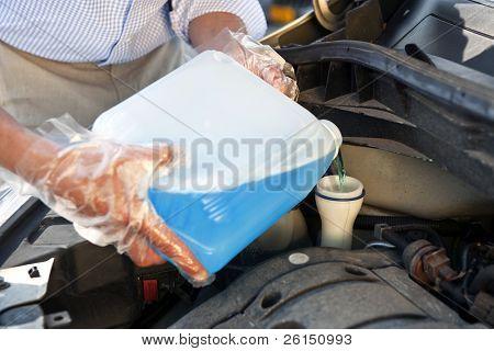 Man wearing plastic gloves, refilling windscreen wiper fluid in his car