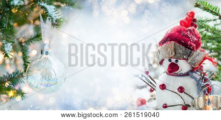 Festive Christmas card with snowman, Christmas bauble and fir branches  on winter background.