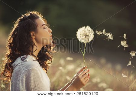 Beautiful Young Woman Sitting On The Field In Green Grass And Blowing Dandelion. Outdoors. Enjoy Nat
