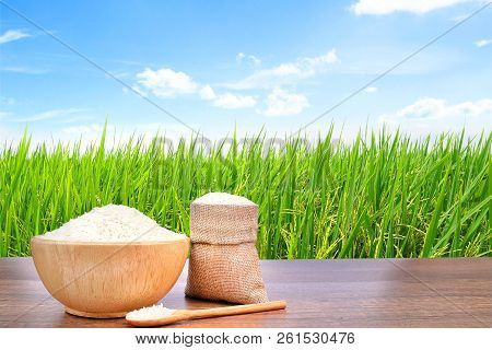 Jasmine Rice (thai Rice) In Wooden Bowl And Sackcloth Burlap On Vintage Wooden Desk Table With The G