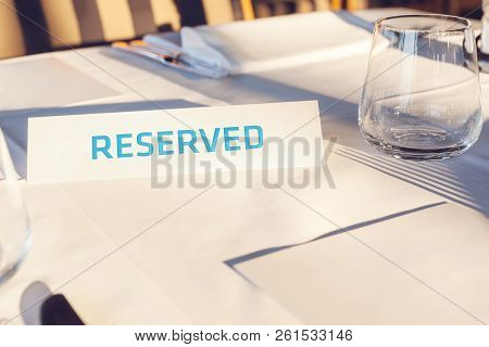 Reserved Table. A Tag Of Reservation Placed On The Wood Table. Reserved Logo. Reservation Sign. Pape