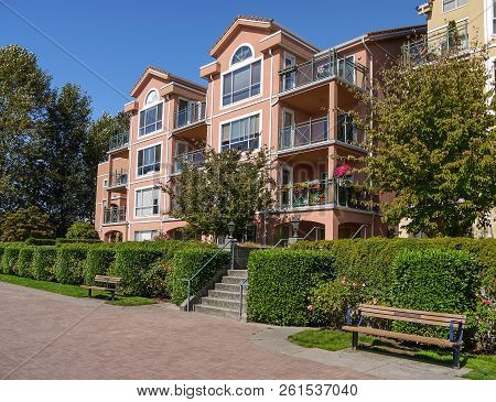 Apartement Building In Residential Area On Sunny Day. Condo Building With Bench And Walkway In Front