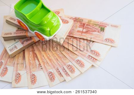 Bank And Russian Money. Car Expenses Concept.toy Car On The Background Of Banknotes.model Of Car Aga