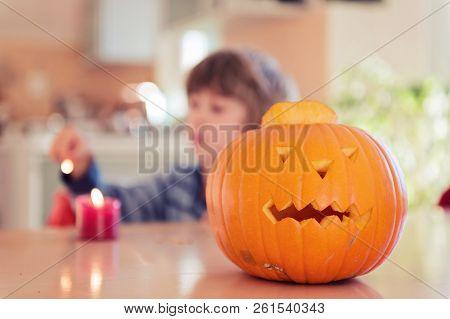 Cute Little Boy Carving Pumpkin On Halloween.