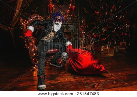 ?heerful punk Santa with a bag of gifts in his hands  in luxurious apartments decorated for Christmas. Bad Santa concept.