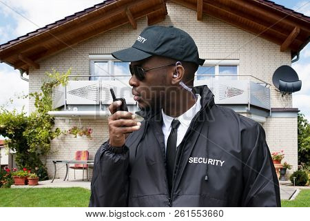 Young African Male Security Guard Talking On Walkie Talkie In Front Of House