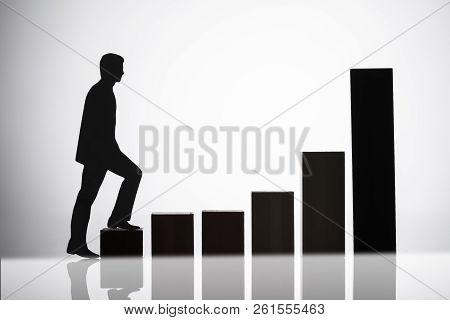 Silhouette Of A Businessperson Walking On Growing Graph Over Reflective Background
