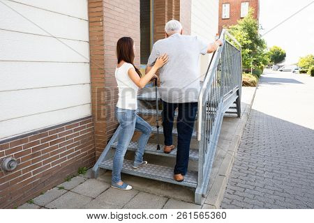 Rear View Of A Young Daughter Assisting Her Senior Father Climbing Staircase