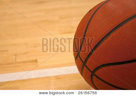 Basketball on hardwood floor angled with room for copy