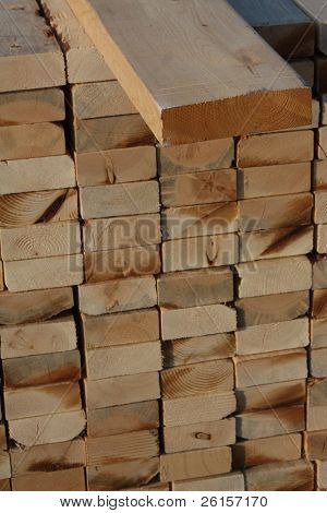 2x4 lying on a stack of wood to be used on a home