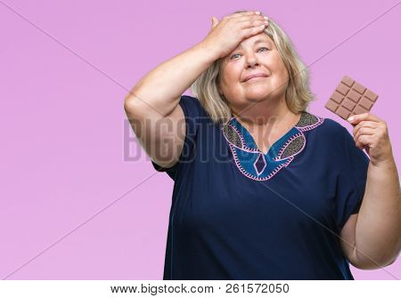 Senior plus size caucasian woman eating chocolate bar over isolated background stressed with hand on head, shocked with shame and surprise face, angry and frustrated. Fear and upset for mistake.