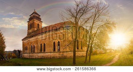 Rainbow Above Panorama Of Abandoned Catholic Church On Hill At Sunset