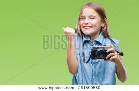 Young beautiful girl taking photos using vintage camera over isolated background screaming proud and celebrating victory and success very excited, cheering emotion